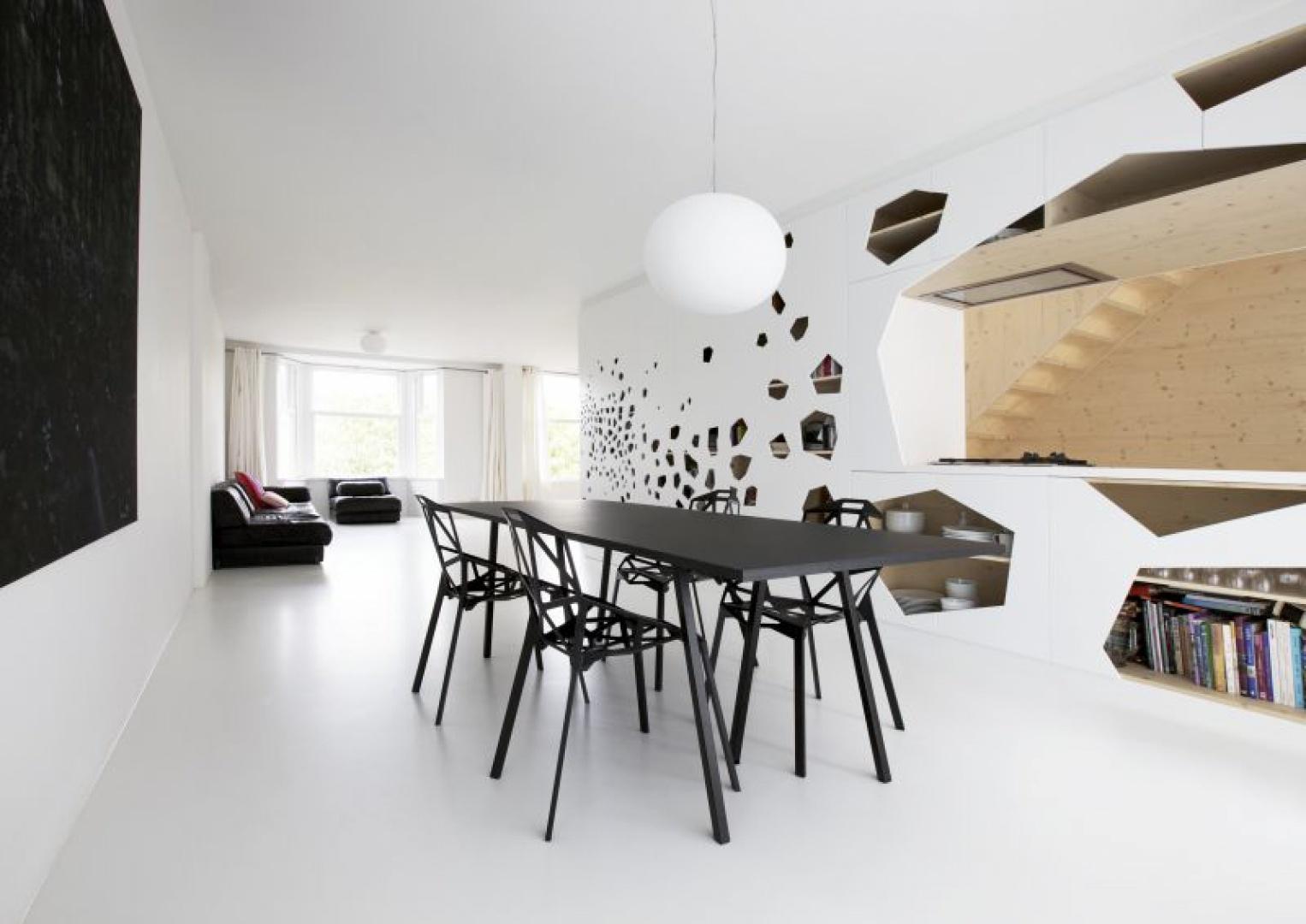 Minimalistyczna koncepcja kolorystyczna sprawiła, że w salonie dominuje biel, czerń i (w tle) brąz drewna. Starą sofę odnowiono, zaś meble dobrano pod kątem dopasowania pod dominujący, ażurowy wzór na ścianie (krzesło Chair One od Magis Constantin Grcic, stół Loop od Hay,  lampa GloBall zaprojektowana przez Jaspera Morrisona z Flos). Fot. i29 l interior architects.