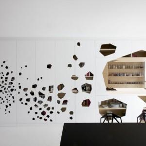 Ażurowa ściana to płyty z MDF-u cięte laserem. Otwory odsłaniają wnętrze szafek kuchennych i schowków (projekt autorski i29, wykonane z jasnego, niemalowanego drewna sosnowego). Fot. i29 l interior architects.