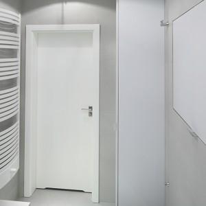 Obie szafki (zapewniają sporo miejsca na przechowywanie i pralkę) wykończone zostały matowym lakierem w kolorze zbliżonym do barwy płytek. Stąd też znakomicie wtapiają się w tło. Fot. Bartosz Jarosz.