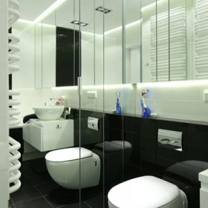 Duże lustrzane fronty skrywają pralkę oraz przestrzeń przeznaczoną na środki czystości. Mniejsze, podwieszane (nad zabudową wc) zapewniają  mnóstwo miejsca na kosmetyki. Fot. Bartosz Jarosz.