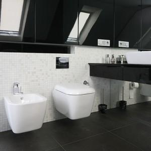 Ogromne lustra oraz połyskujące fronty szafek wizualnie powiększają łazienkę.  Jedno z luster przyklejono na  ścianie pod konsolą, na której stoi umywalka. Fot. Bartosz Jarosz.