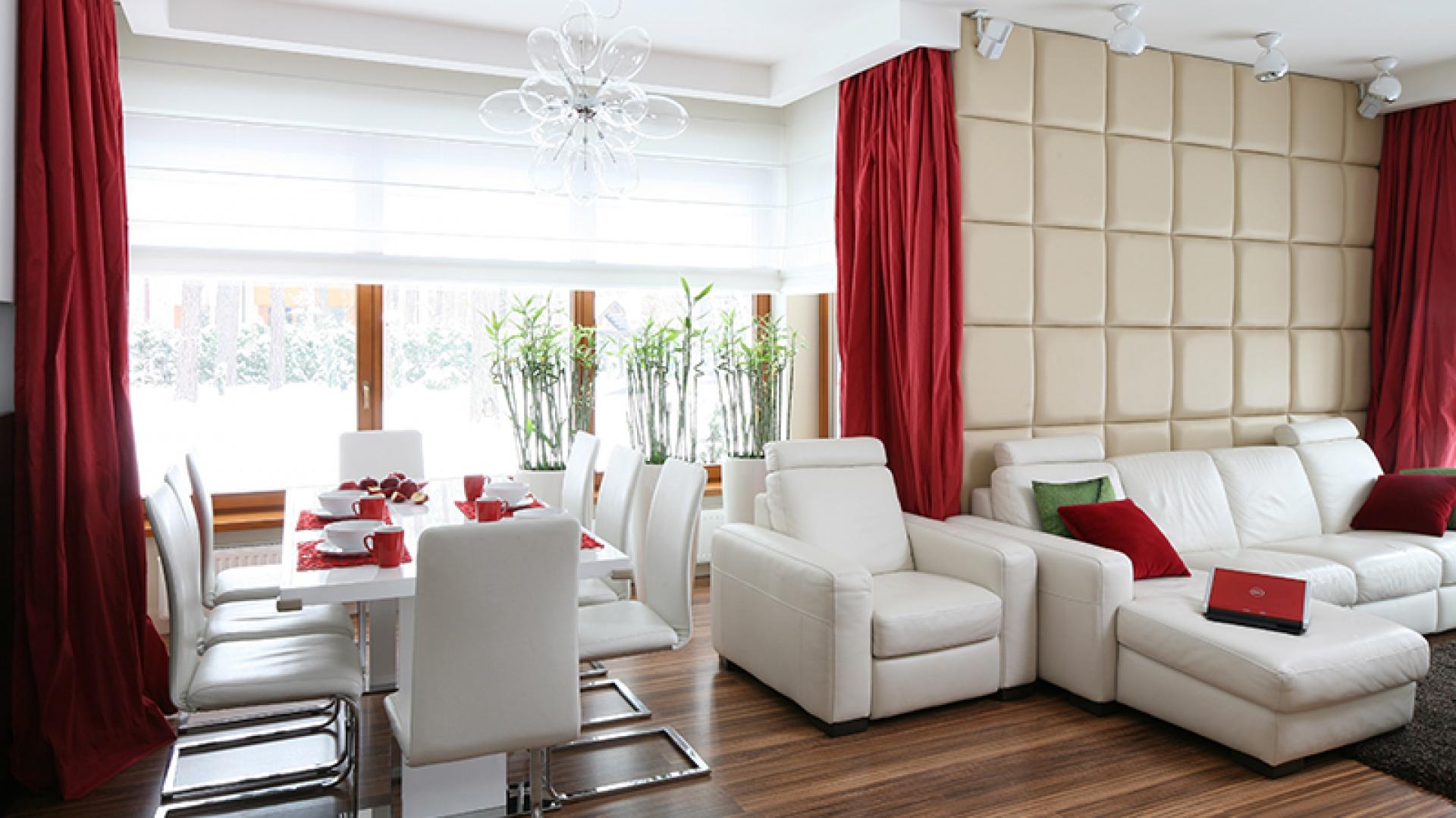 Otwarta przestrzeń dzienna tworzy jedną, spójną stylistycznie całość. Poszczególne strefy spaja uniwersalna biel – ulubiony   kolor właścicielki. Mocne, czerwone akcenty przełamują jej monochromatyczność. Fot. Bartosz Jarosz.