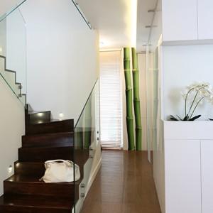 Na piętro prowadzą drewniany schody zabezpieczone szklaną balustradą. Fot. Bartosz Jarosz.