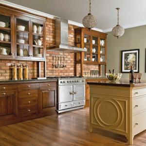 Manhattan – fronty szafek wykonane z litego, patynowanego drewna dębowego; szklane witryny i niewielkie uchwyty dodają ciemnym meblom delikatności; klasyczna wyspa w kolorze jaśminu kontrastuje oraz równoważy ciężkość dębowych szafek. Wycena indywidualna, Fabryka Wnętrz.