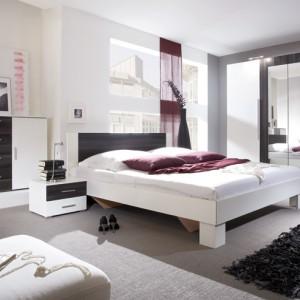 Łóżko z sypialni Vera to połączenienowoczesnego designu oraz materiałów wykonanych w najnowszych technologiach. Kolorystyka: biały/orzech czarny. Wycena indywidualna, HM Helvetia Meble