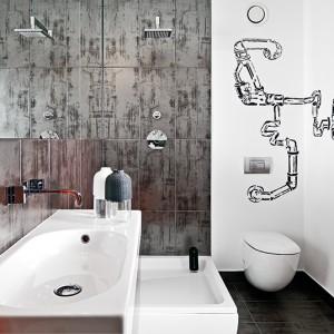 Łazienka w industrialnym stylu mieści zarówno wannę, jak i prysznic. Duże lustro jeszcze optycznie powiększa jej przestrzeń.