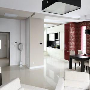 """Kuchnia ma charakter przechodni – można do niej  wejść z holu oraz salonu i jadalni. Na podłodze – biały gres, na ścianie nad blatem roboczym – czarny z serii """"Concept"""" Nowa Gala. Z tej perspektywy wzrok zatrzymuje się na bordowym pasie zabudowy kuchennej i jadalni. Fot. Serwis Prasowy Diamentic Estate."""