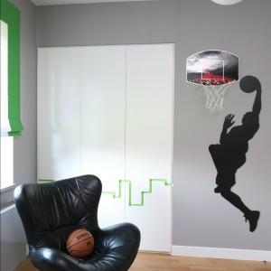 Z hobbystyczną aranżacją ściany koresponduje oświetlenie. Zwisające z sufitu lampy swoim kulistym kształtem przypominają piłki. Fot. Bartosz Jarosz.
