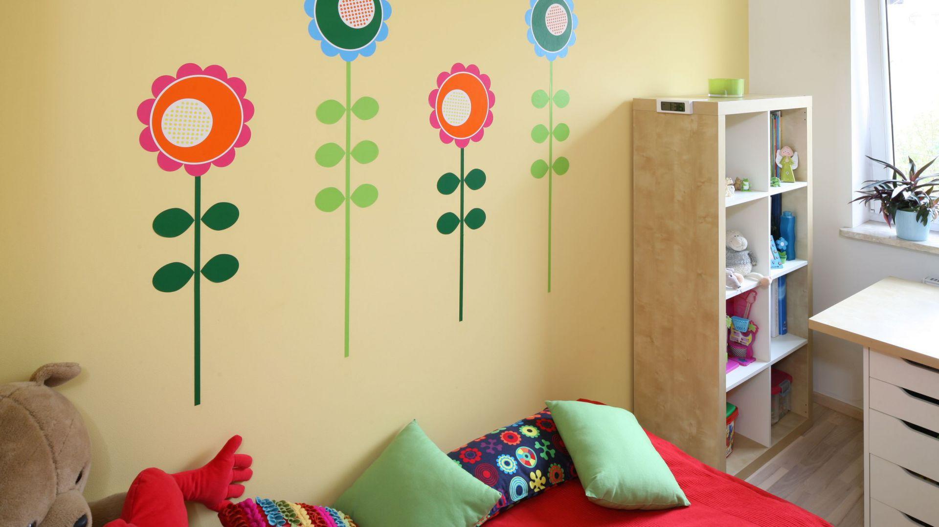 Najbardziej wiosennym miejscem w pokoju jest to, przeznaczone do snu. Bujne kwiaty zdobią nie tylko kolorowe poduchy, ale i ścianę przy łóżku dziewczynki. Fot. B. Jarosz.