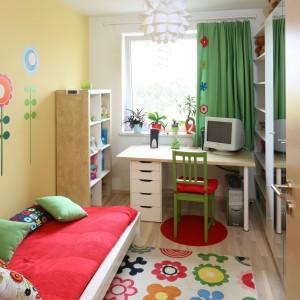 W najjaśniejszym miejscu pokoju ustawiono jasne biurko oraz zielone, proste krzesło wyścielone czerwoną poduszką. W słoneczne dni nadmiar światła zatrzyma zasłona w kolorze świeżej trawy, którą zdobią aplikacje identyczne jak kwiaty na dywanie. Fot. B. Jarosz.