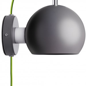 Lampa ścienna Ball marki BoConcept dostępna w trzech wersjach kolorystycznych. Świetnie sprawdzi się w nowoczesnych sypialniach.Na zdjęciu kinkiet wykonany z ciemnoszarego metalu z przewodem z zieloną powłoką tekstylną.Fot. BoConcept