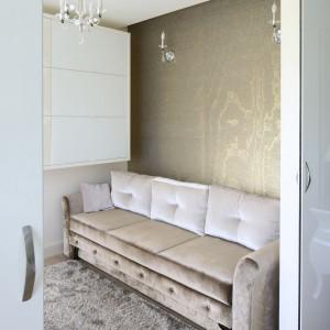 Dokładnie naprzeciwko biurka ustawiona została sofa tapicerowana tą samą tkaniną, co krzesło. Ścianę za sofą zdobi tapeta Caparate, firmy Arte. Fot. Bartosz Jarosz.