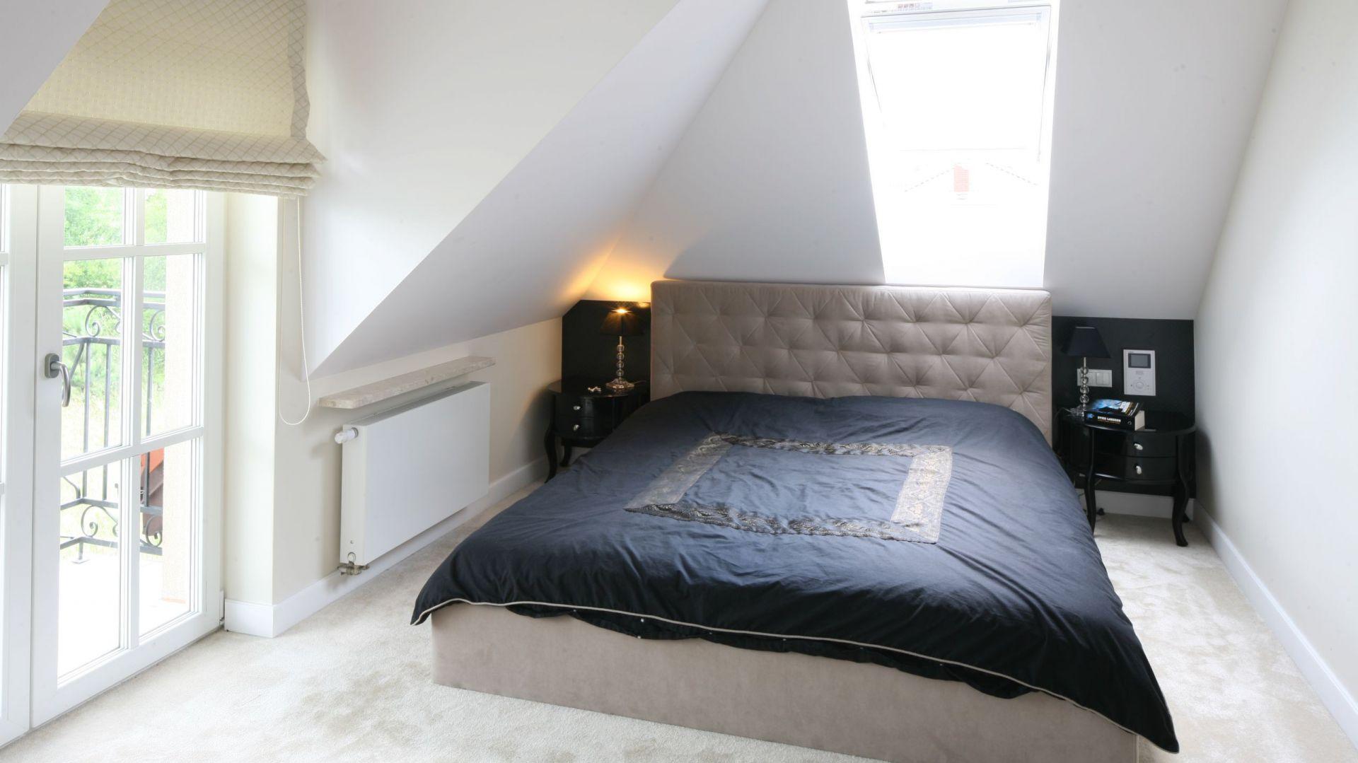 Skosy spowodowane kształtem więźby dachowej, nie ułatwiają zadania projektantom wnętrz. W sypialni udało się wpasować wygodne łóżko z szafkami nocnymi po obu stronach. Fot. Bartosz Jarosz.