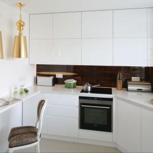Bardzo nowoczesna linia kuchni ciekawie koresponduje z klasyką salonu. Bezuchwytowy system szafkowy zapewnia czystą formę. Złoty kolor lamp ciekawie przełamuje sterylność wnętrza. Fot. Bartosz Jarosz.