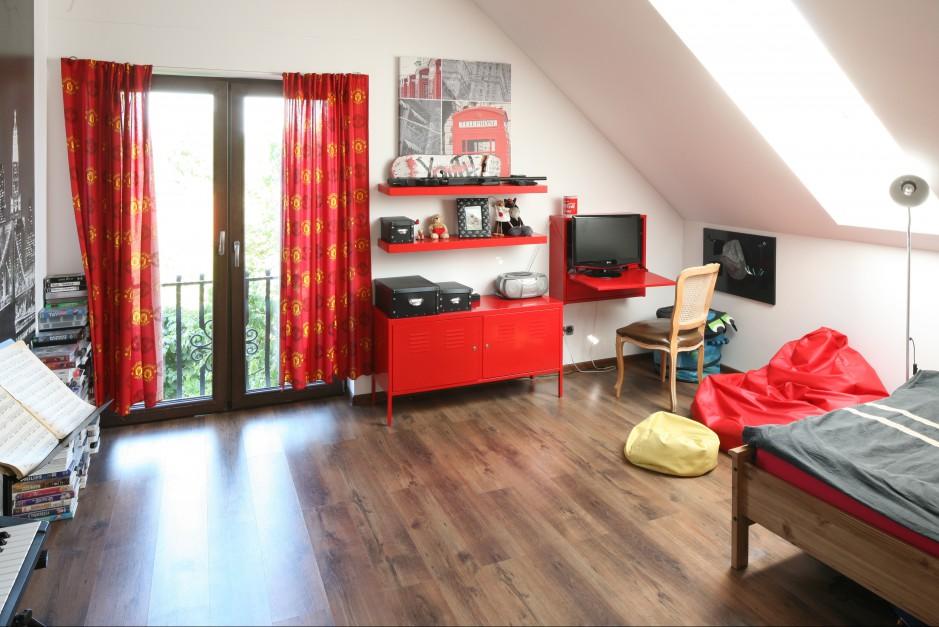 Ciemnobrązowe panele ułożone na podłodze idealnie  korespondują z dominującą w pokoju czerwienią. Fot. Bartosz Jarosz.