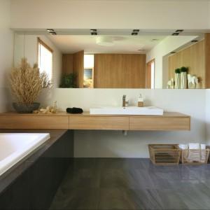 Łazienka jest wygodna i przestronna; wydzielono tutaj także aneks na pralnię. Lustro oraz blat podumywalkowy zajmują całą szerokość ściany. Fot. Bartosz Jarosz.