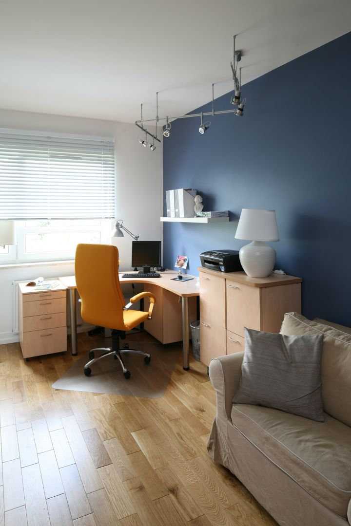 Mimo tego, że biurko znajduje się przy ciemnej ścianie miejsce pracy jest należycie oświetlone. Dopływ światła dziennego zapewnia duże okno, a po zmroku - żyrandol i lampka stojąca na szafce. Fot. Bartosz Jarosz.