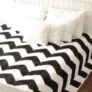 Patchworkowa  narzuta UTHE z mocnym  czarno- białym zygzakiem ożywi każdą sypialnię. Narzuta dwustronna - z drugiej strony biała z jednym, czarnym zygzakiem. Fot. Patchwork House.