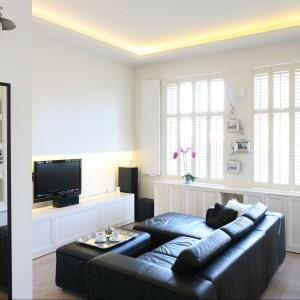 Drewniane shuttersy przysłaniające okna w salonie są bardzo gustownym elementem dekoracyjnym. Ich biała kolorystyka tworzy harmonijną całość z meblami i ładny kontrast z czarną kanapą. Fot. Bartosz Jarosz.