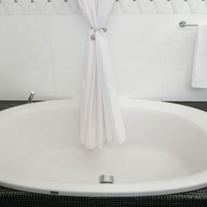 Nie było miejsca na oddzielną wannę i prysznic. Obie te funkcje połączono, rolę tradycyjnej kabiny pełni tu biała zasłona. Fot. Bartosz Jarosz.