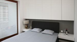 W tej sypialni panuje wyjątkowy spokój i równowaga. Biel, szarość i czerń - modne zestawienie barw sprawdza się tutaj znakomicie.