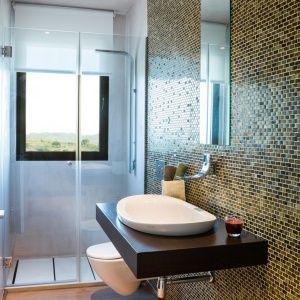 Kolejna z łazienek, tym razem z neutralną w kolorystyce mozaiką i ponownie - z podłogą z drewna. Fot. Gori Salvà.