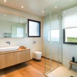 Łazienka nowoczesna, ale blisko natury - kabina bez brodzika, piękna umywalka meblowa, szkło i drewniana podłoga dodają jej charakteru. Fot. Gori Salvà.