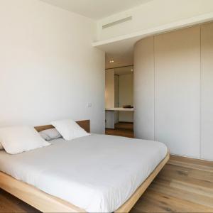 Biała, nowoczesna sypialnia stanowi inspirujący miks drewna i neutralnych beży. Wszystko ma tu swoje miejsce. Fot. Gori Salvà.