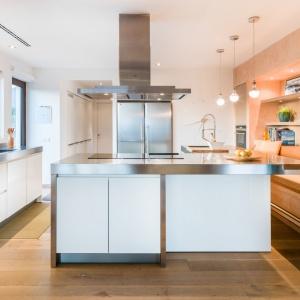 Otwarta na salon kuchnia z dużą wyspą kuchenną i zabudową kuchenną na wysoki połysk. Fot. Gori Salvà.