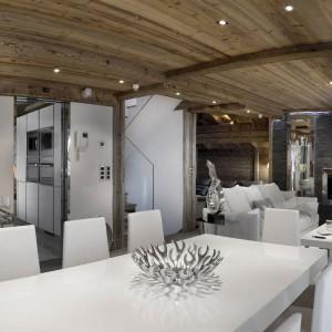 Rzut oka na otwartą przestrzeń dzienną. Biały stół i krzesła w jadalni podkreślają jej nowoczesny charakter. Fot. Chalet Eden Courchevel.