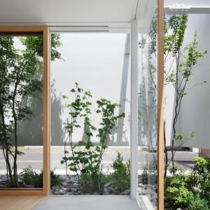 Oszczędna aranżacja rodem z japońskich ogrodów: biel, drewno i roślinność. Fot. Nacasa & Partners Makoto Yasuda.