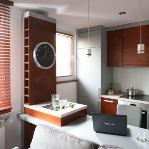 Drewniana, brązowa zabudowa kuchenna kontrastuje z minimalistycznymi szarościami. Fot. Bartosz Jarosz.