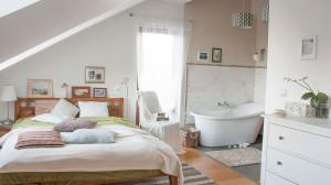 Kobieca sypialnia połączona z salonem kąpielowym. Właścicielka tego wnętrza postawiła na naturalne drewno i biel, a wanna zaglądająca do sypialni to ulubiony fragment mieszkania.