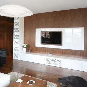 Pomysł na ściankę telewizyjną - fornir orzechowy oraz białe szafki z ażurowymi frontami, skrywające m.in głośniki. Fot. Bartosz Jarosz.