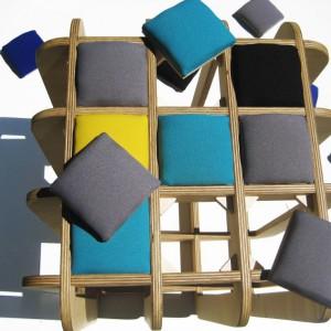 Siedzisko sześcian Poduszak zbudowany z 8 zaplecionych modułów ze sklejki brzozowej. Krzyżujące się części tworzą kwadratowe, puste obszary na miękkie poduszki. Dzięki poduszkom siedzisko jest wygodne i nabiera ciekawego, indywidualnego wyglądu. Poduszki można układać w dowolne kompozycje kolorystyczne i fakturowe, w zależności od upodobań i humoru. Fot. Tabanda.