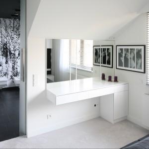 Za przesuwnymi drzwiami ukrywa się prywatna łazienka. Między dwoma pomieszczeniami spotykamy kontrast między jasną wykładziną z sypialni a ciemnymi płytkami w łazience. Proj. Dominik Respondek. Fot. Bartosz Jarosz.