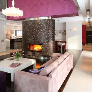 Kominek stanowi wyraźną część rozgraniczającą salon od jadalni. Nad nim stworzono konstrukcję, skrywającą odprowadzenie i wentylację, pokrytą barwną tapetą. Fot. Bartosz Jarosz.