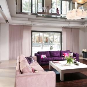 Salon wyznacza linia parkietu, na którym jak na dywanie usytuowano kanapy, kominek i stół. Gres, ułożony wzdłuż ścian, podkreśla linię ciągu komunikacyjnego. Fot. Bartosz Jarosz.