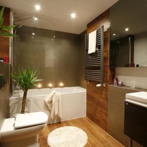 Pod obniżeniem nadbudowanej stalowej konstrukcji tuż przy wejściu do mieszkania zaprojektowano nowoczesną łazienkę. Wanna nadaje łazience rys elegancji. Obudowana śnieżnobiałą mozaiką, jest silną przeciwwagą dla przeważających tu ciemnych i dużych płyt.  Fot. Marcin Onufryjuk.