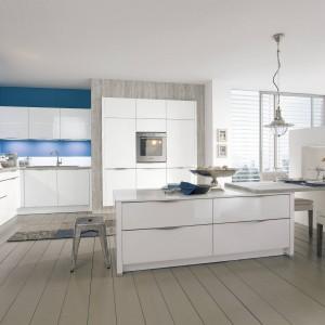 Kuchnia z kolekcji 888 Vitus. Nowoczesna, prosta w formie i funkcjonalna. Fronty wykonane ze szkła są lekkie i ładnie pasuję do mocnego koloru zastosowanego na ścianie. Wycena indywidualna, Wellmann.