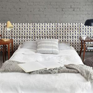 Cegła pomalowana na jednolity kolor tworzy ciekawe tło dla tapicerowanego zagłówka. Fot. Made For Bed.