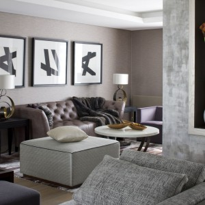 Wykonaną na zamówienie, pikowaną skórzaną sofę ulokowano pod trzema charakterystycznymi, biało -czarnymi dziełami sztuki niemieckiego artysty Godwina Hoffmana. Dwa niskie fotele firmy Meridiani i biały, lakierowany stolik kawowy od Porta Romana dopełniają całości. Fot. Richard Waite.