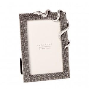 Ramka na zdjęcie w kolorze srebra ze wzorem węża. Sprzedaż: Zara Home, cena: 89,90 zł.