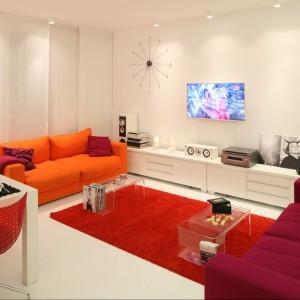Białe podłogi i ściany wydobyły cały urok kolorowych mebli i dodatków. Obok czerwieni pojawiają się tu pomarańcze i róże, ale wszystkie barwy świetnie ze sobą współgrają. Proj. wnętrza Katarzyna Mikulska-Sękalska.