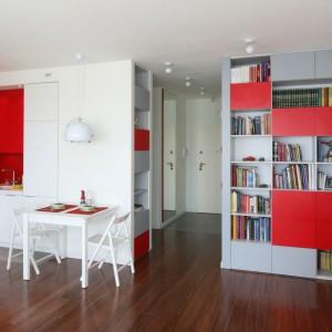 Proj. wnętrza Iza Szewc, Fabryka Nastroju. Intensywny czerwony kolor pojawia się jako fronty w nowoczesnym regale oraz - w kontraście do białych szafek - jako część kuchni.