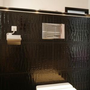 Surowy ton łazienki łagodzi pomalowana na czarno rama do obrazu w stylu Ludwika XIV, pojawiająca się jako niebanalna oprawa dużego lustra. Fot. Bartosz Jarosz.