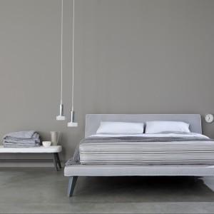 Szara ściana i  meble o prostej formie tworzą minimalistyczną sypialnię. Fot. Letti&Co.