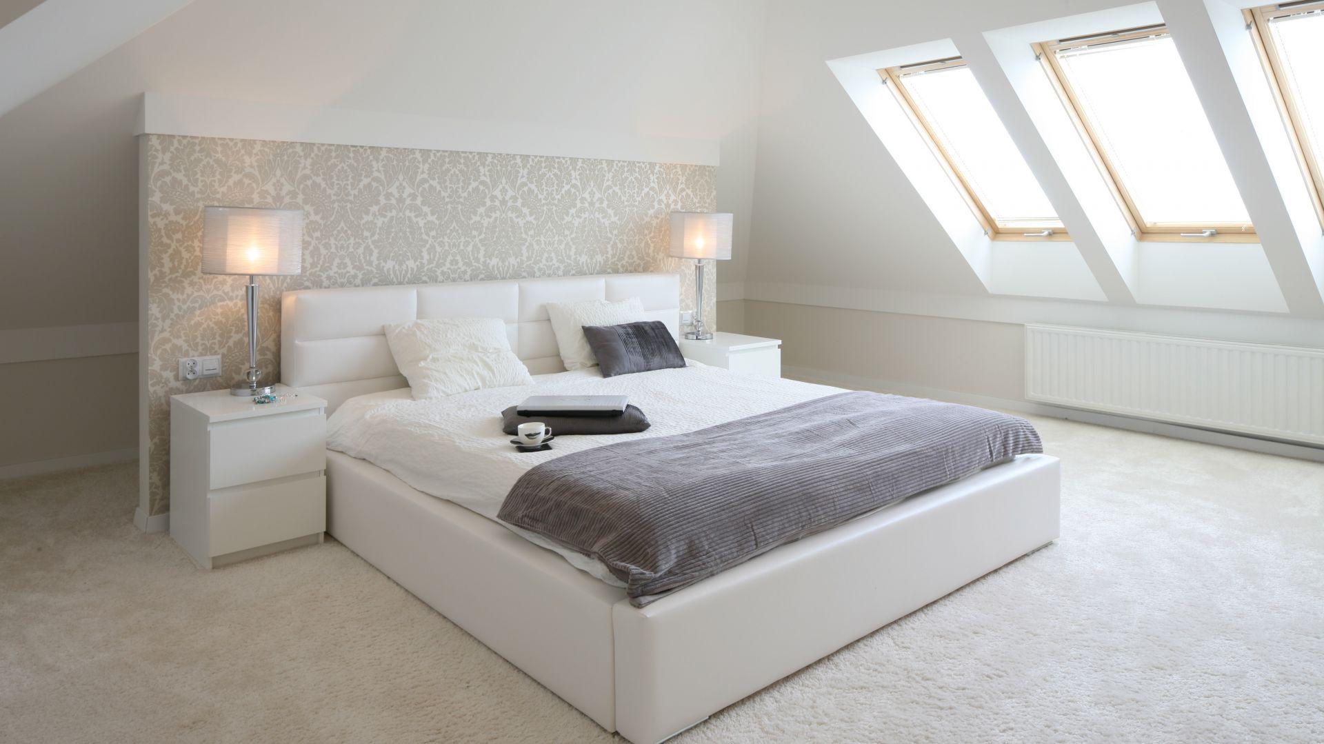 Beżowa ściana kolankowa oraz delikatna tapeta na ścianie w połączeniu z  jasnymi tkaninami tworzą przytulną sypialnię . Proj. Karolina i Artur Urban. Fot. Bartosz Jarosz.