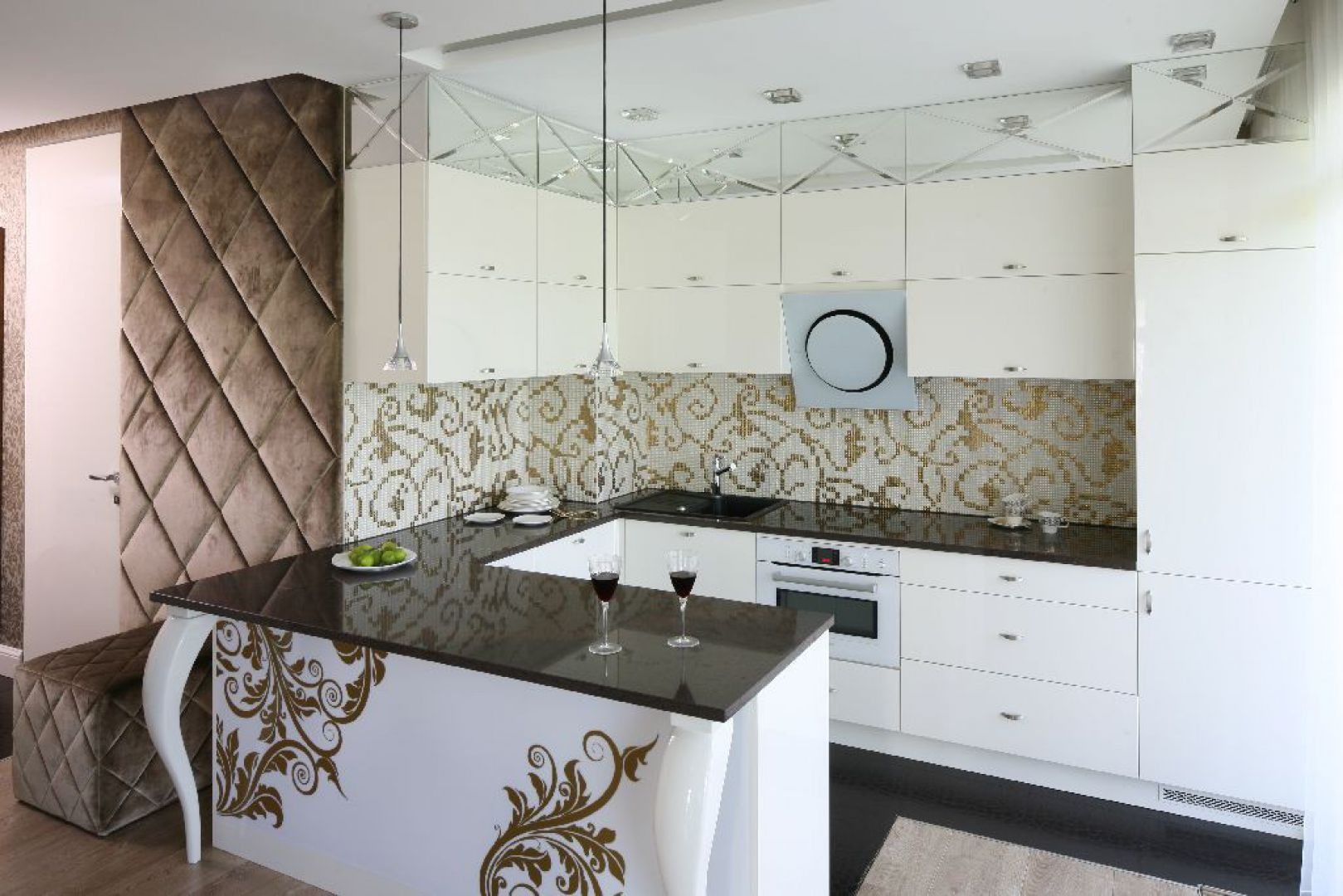 """Spokojny kolor """"złamanej"""" bieli jest doskonałym tłem dla mocno dekoracyjnych elementów mieniących się złotem – mozaiki nad blatem oraz grafiki na ladzie. Fot. Bartosz Jarosz."""