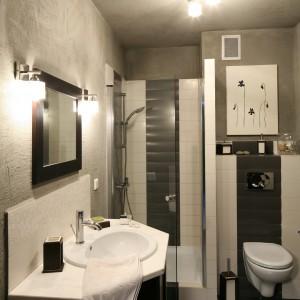 Płytki ceramiczne występują tylko w mokrych strefach pomieszczenia oraz na podłodze. Resztę ścian oraz sufit wykończono tynkiem strukturalnym przypominającym niedbale zaciągniętą szpachlę. Wyposażenie: drzwi prysznicowe Aquaform. Fot. Bartosz Jarosz